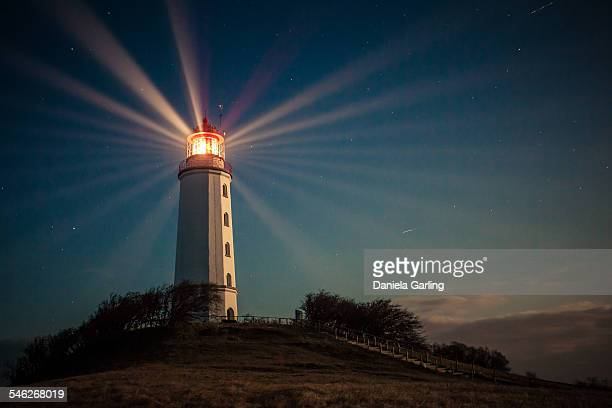 Lighthouse on a hill shining at night