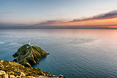 South Stack lighthouse in Holyhead, Anglesey, North Wales. The lighthouse sits on top of a rock island with white walls which lead people to the lighthouse. The photograph was taken on a summer evenin