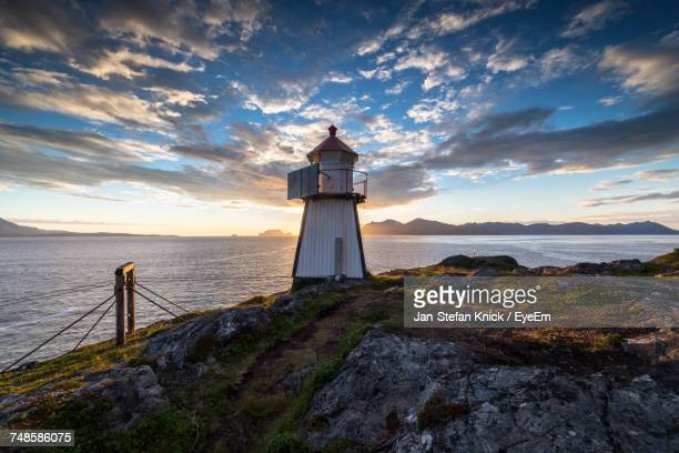 Lighthouse On Rock Formation By Sea Against Sky During Sunset