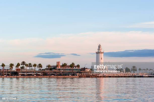 Lighthouse on the shoreline of Palmeral de las sorpresas port in Malaga, Andalusia, Spain.