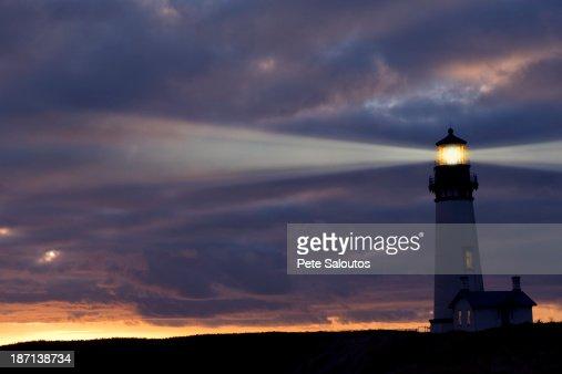 Lighthouse shining against cloudy sky