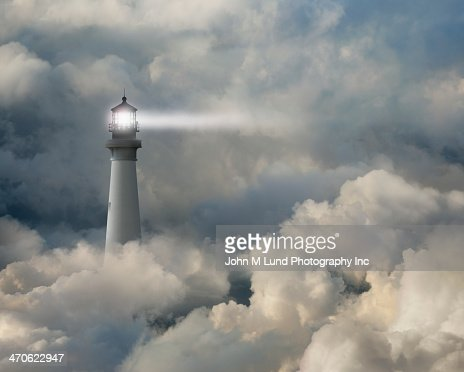 Lighthouse shining beam into thick clouds