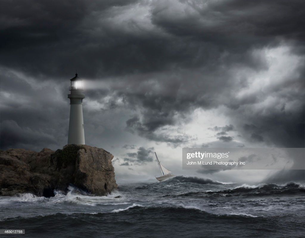 Lighthouse shining over stormy ocean : Stock Photo