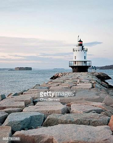 A lighthouse stands guard over the entrance to a harbor.
