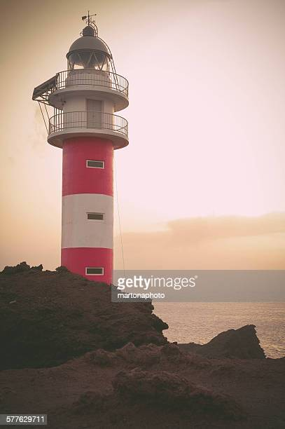 Lighthouse with red and white stripes in sunset