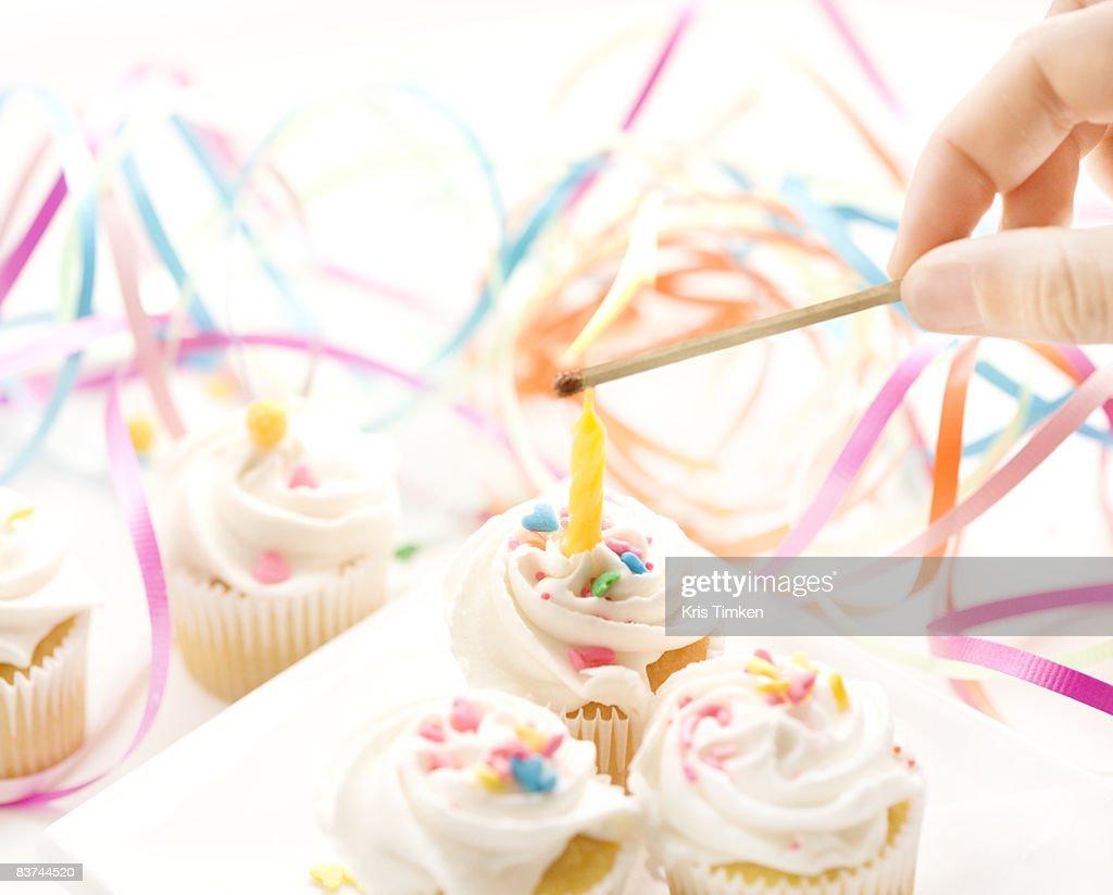 lighting candle on mini cupcake : Stock Photo