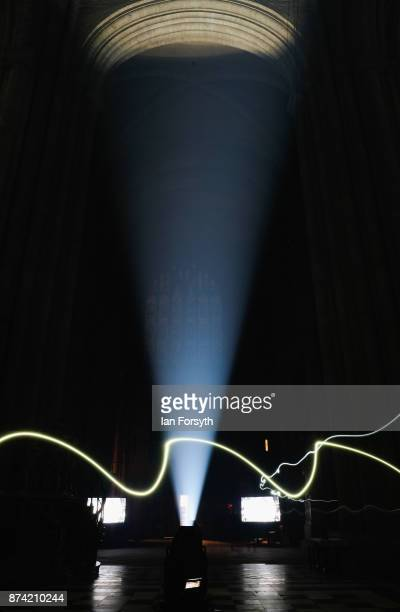 A lighting engineer wearing a head torch walks through the picture as the inside of the historic Durham Cathedral is illuminated by a light...