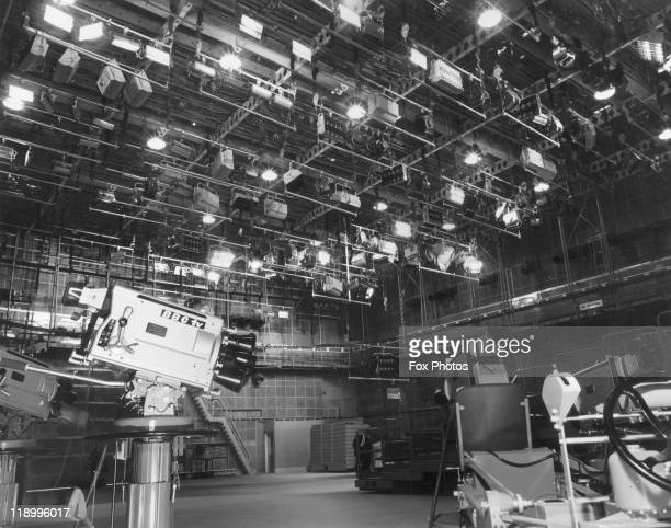 Lighting rigs line the celiling with a BBC TV camera in the foreground in the television studio from which the first programme was transmitted from...
