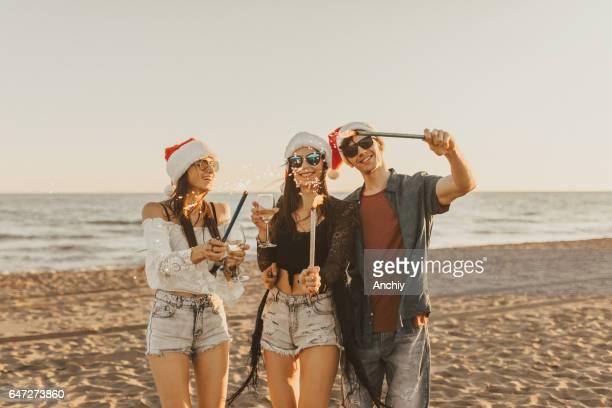 Lighting sparklers on the beach, santa hats