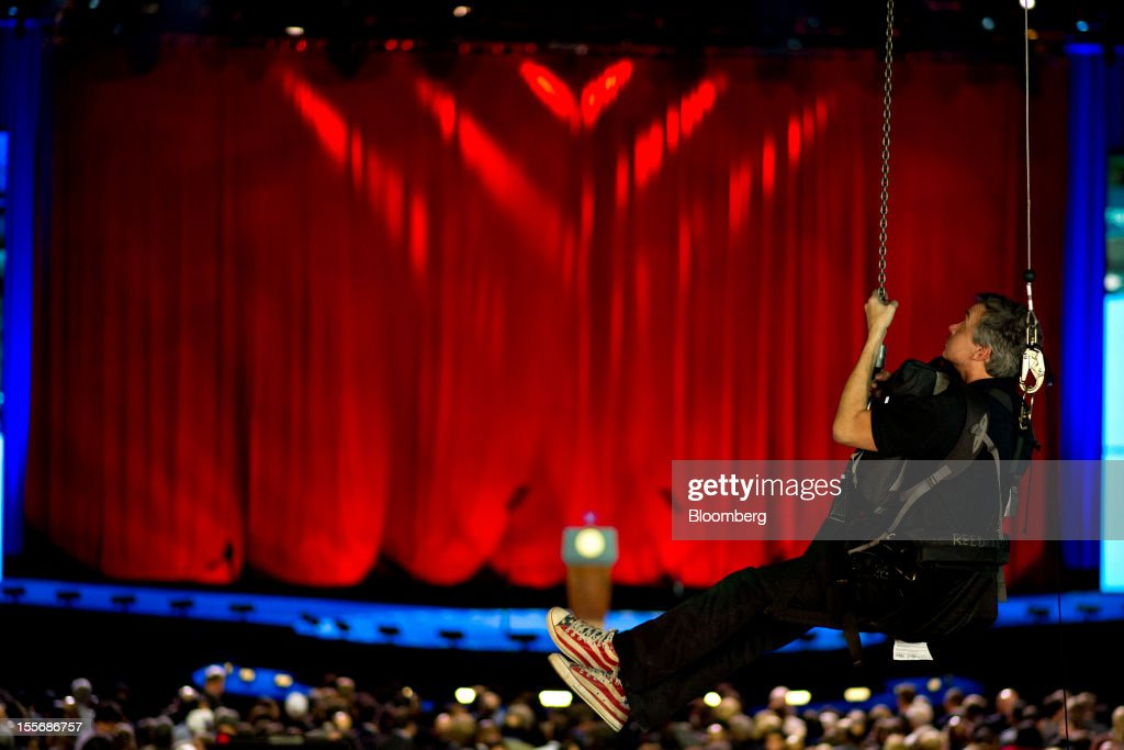 A lighting technician is hoisted to an overhead platform during an election night rally for U.S. President Barack Obama in Chicago, Illinois, U.S., on Tuesday, Nov. 6, 2012. Obama was projected the winner in the battleground states of Wisconsin and New Hampshire, according to television networks, as well as in Pennsylvania, thwarting Republican challenger Mitt Romney's late bid for a victory in that state. Photographer: Daniel Acker/Bloomberg via Getty Images