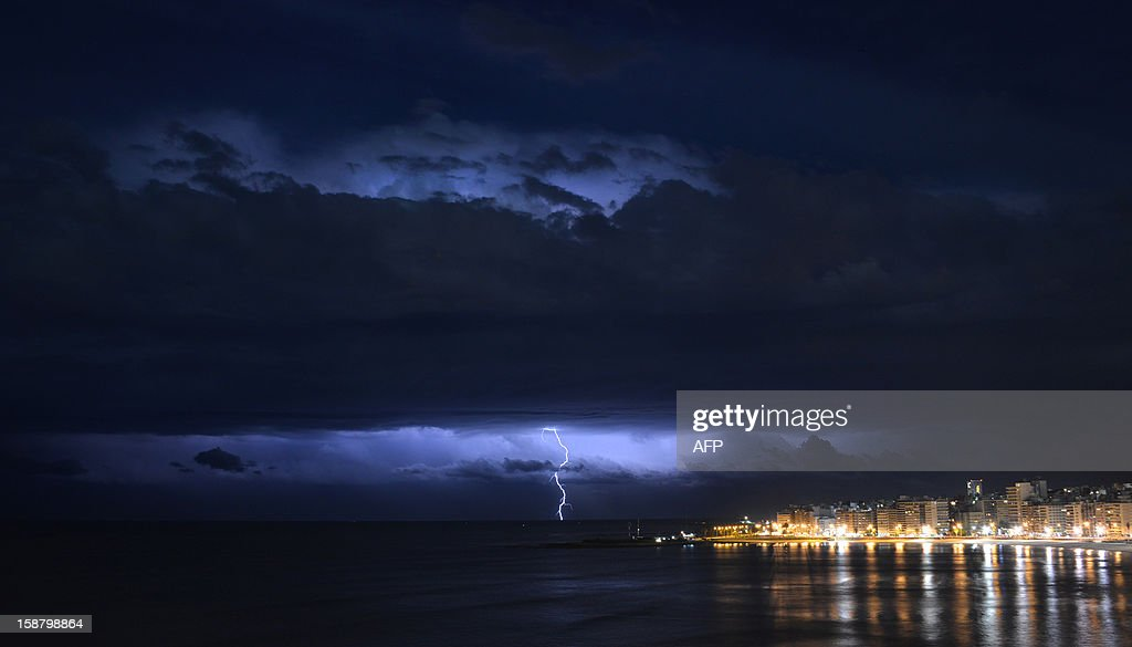 A lightning bolt flashes on the horizon over the River Plate off the coast of Montevideo, Uruguay, early on December 29, 2012. AFP PHOTO/MARIANA SUAREZ
