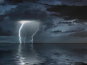 lightning bolts reflection over the sea. taken during a thunderstorm over the ocean with clouds in the background