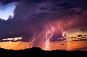 Powerful lightning bolts strike from a sunset thunderstorm in the Arizona desert.