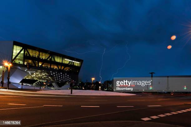 Lightning flashes during a thunderstorm above the headquarters of Porsche AG right and the company's automobile museum left in Stuttgart Germany on...