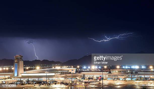 Lightning flashes east of a ground control tower at McCarran International Airport during a thunderstorm on July 6 2015 in Las Vegas Nevada The...