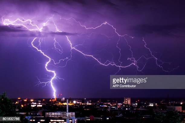 TOPSHOT Lightning flashes over Munich southern Germany on June 26 2017 / AFP PHOTO / dpa / Marcel Kusch / Germany OUT