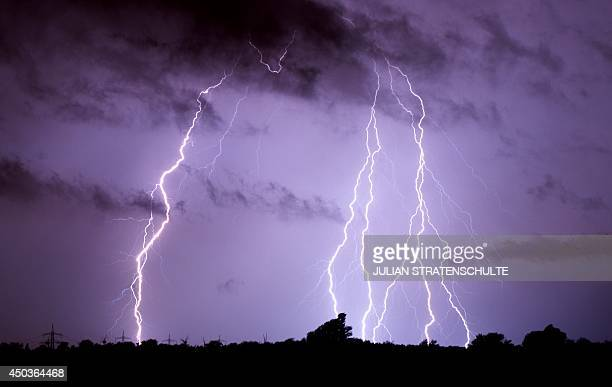 Lightning is pictured on June 10 2014 over Algermissen Germany Violent storms killed at least six people in western Germany overnight felling trees...