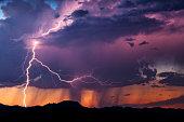 Lightning illuminates an isolated thunderstorm at sunset in the Arizona desert.