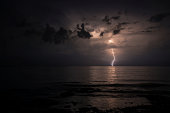 Bolt of lightning over the sea at night during a thunderstorm.