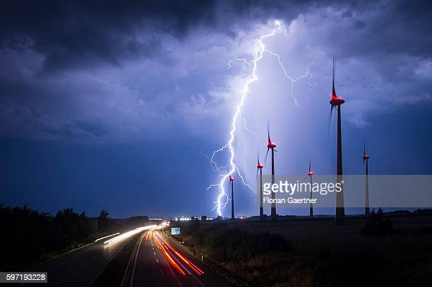 Lightning strikes behind wind turbines during a thunderstorm near the border between Germany and Poland on August 28 2016 in Goerlitz Germany After a...