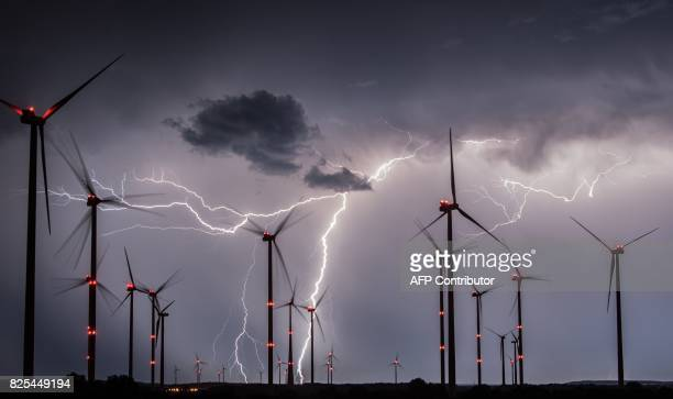 TOPSHOT Lightnings flash over windmills of the Odervorland wind energy park near Sieversdorf eastern Germany on August 1 2017 / AFP PHOTO / dpa /...