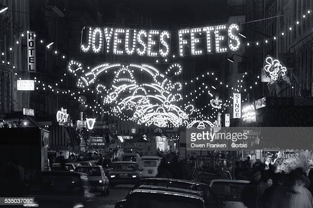Lights above Market Street in the 18th Arrondissement read 'Joyeuses Fetes' at Christmastime