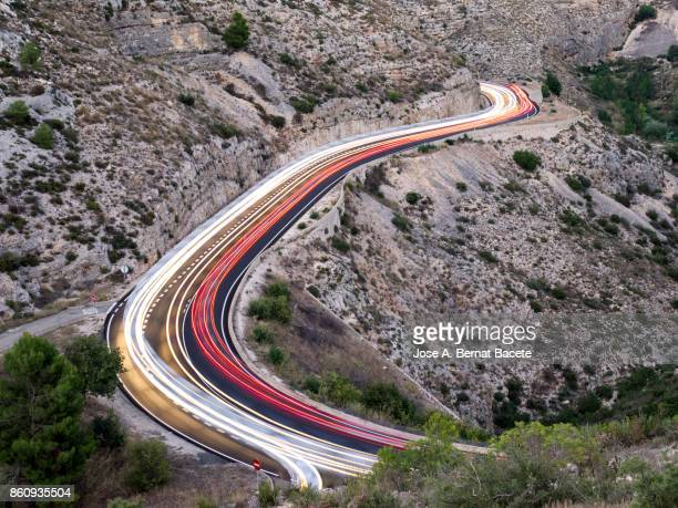 Lights and trails of vehicles circulating along a road of mountain with curves closed in the sunset. Valencian Community, Spain
