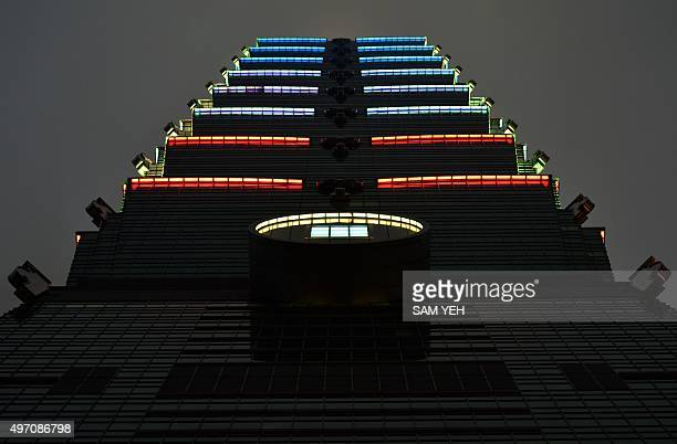 Lights are lit with the colours of the French flag on the Taipei 101 building in Taipei on November 14 in honour of the victims killed in a spate of...