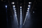 Many Par Led Lights beams Spotlight ray moving lighting on rack construction ceiling, for Fashion Show Event performance in dark room hall for fashion show style decorated floor