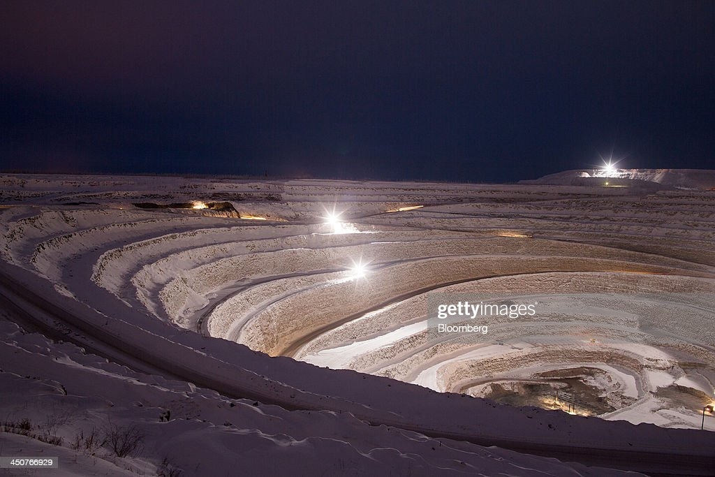 Lights from working vehicles illuminate the open pit of the Nyurbinsky diamond mine operated by OAO Alrosa in Nakyn, Russia, on Friday, Nov. 15, 2013. OAO Alrosa, the world's largest diamond producer, raised about $1.3 billion in an oversubscribed share sale from investors including Oppenheimer Funds Inc. and Lazard Ltd.'s asset-management unit, First Deputy Prime Minister Igor Shuvalov said. Photographer: Andrey Rudakov/Bloomberg via Getty Images