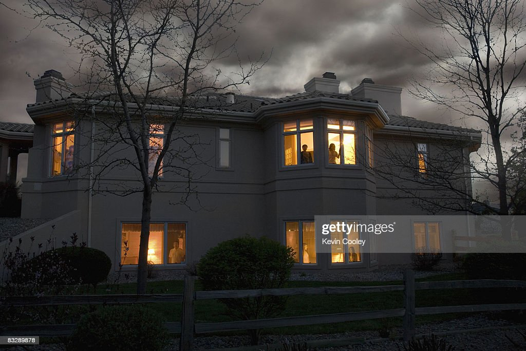 Lights glowing in suburban house : Stock Photo