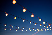 String lights hang outdoors on a summer evening.