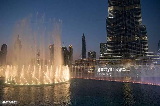 Lights illuminate a water fountain show outside the Dubai Mall at the base of the Burj Khalifa tower right in Dubai United Arab Emirates on Saturday...