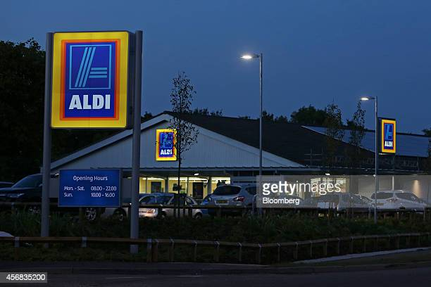 Lights illuminate Aldi logos as they stand outside an Aldi discount supermarket operated by Aldi Stores Ltd at dusk in Chelmsford UK on Tuesday Oct 7...