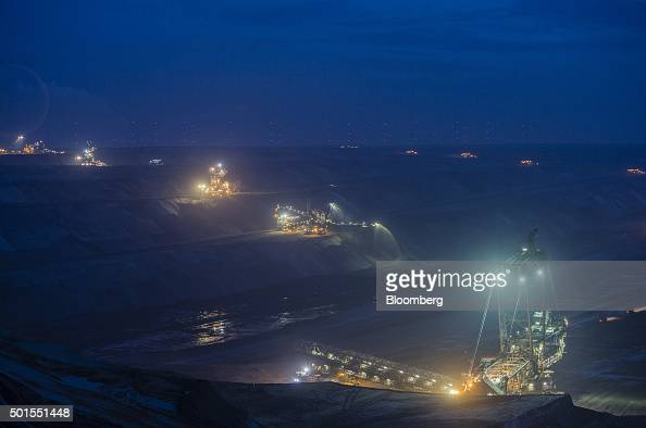 Lights illuminate giant excavators as they operate at dusk at the Garzweiler open cast lignite mine operated by RWE AG in Garzweiler Germany on...