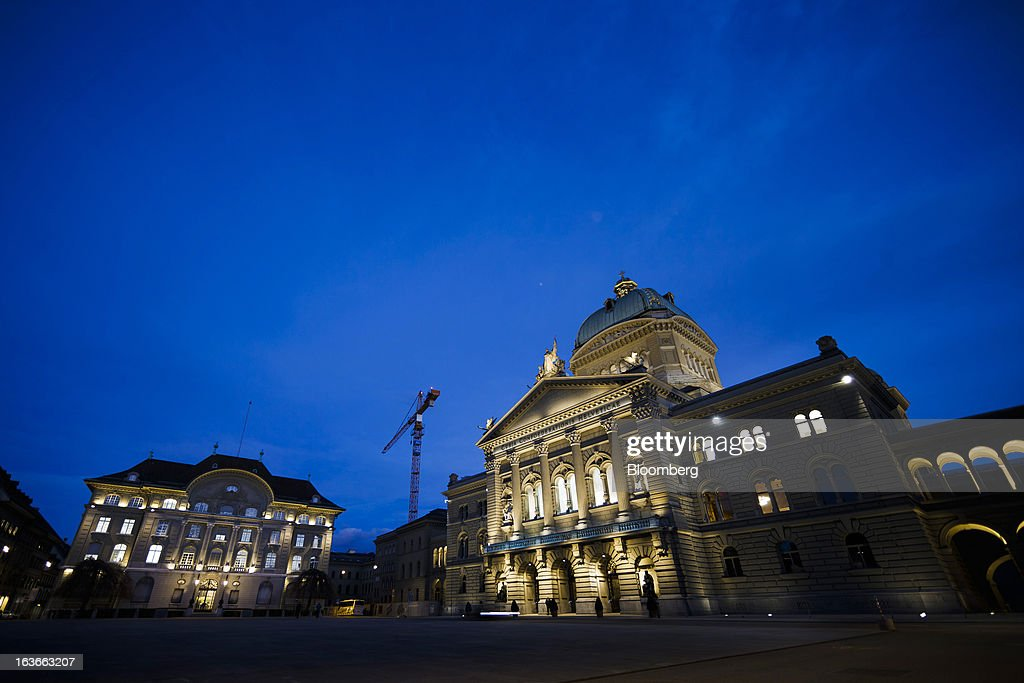 Lights illuminate the front of the Swiss National Bank (SNB), Switzerland's central bank, left, and the Federal Palace, Switzerland's parliament building in Bern, Switzerland, on Tuesday, March 12, 2013. The Swiss central bank pledged to keep up its defense of the franc cap after almost doubling its currency holdings to shield the country from the fallout caused by the euro zone's crisis. Photographer: Valentin Flauraud/Bloomberg via Getty Images
