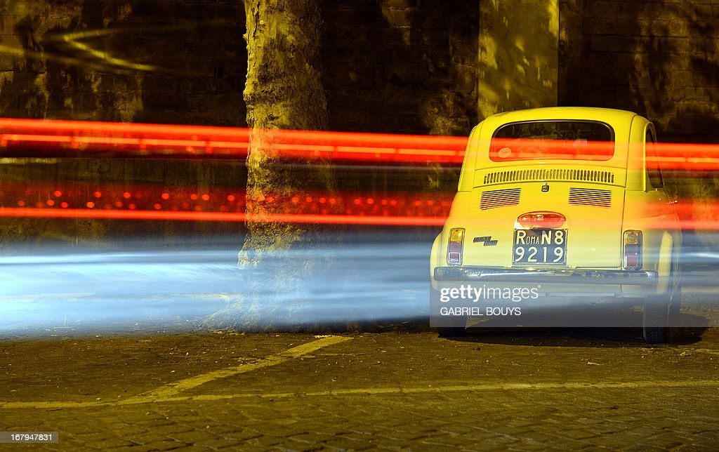 Lights of cars are seen as a Fiat 500 is parked in a street of Rome on May 2, 2013. The Fiat 500, the Cinquecento small and practical car designed by Dante Giacosa, was produced by the Italian carmaker Fiat from 1957 to 1975. AFP PHOTO / GABRIEL BOUYS