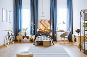 Lights on a metal frame of the bed in white and blue bedroom interior for a boy