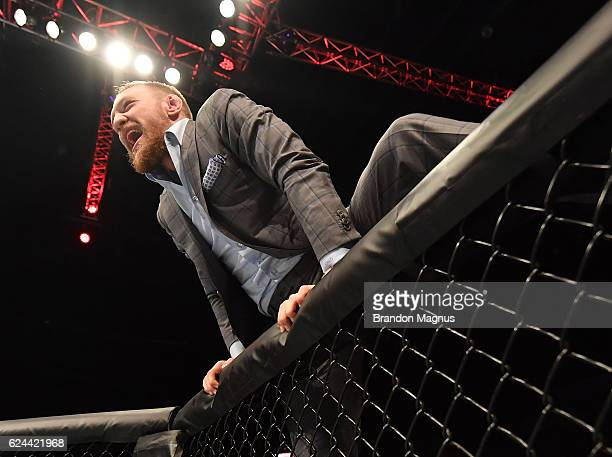 UFC lightweight and featherweight champion Conor McGregor climbs into the Octagon to celebrate with teammate Artem Lobov after his featherweight bout...