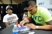 UFC lightweight champion Anthony Pettis signs autographs for fans during the UFC Fan Expo 2014 during UFC International Fight Week at the Mandalay...
