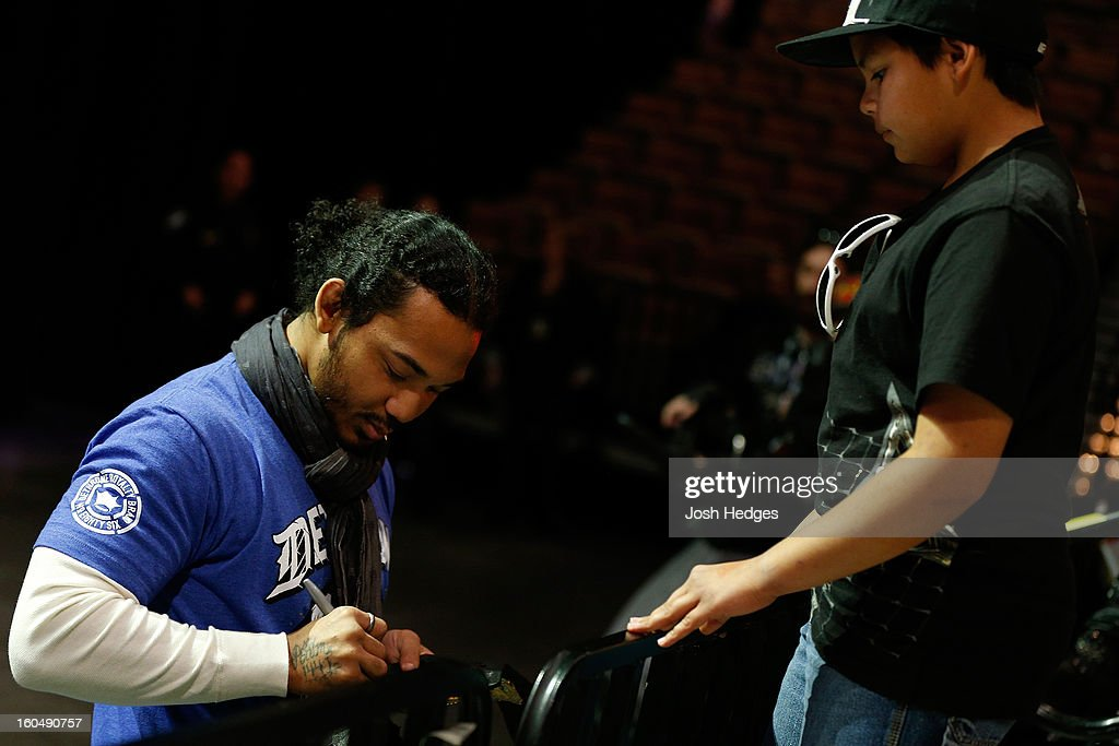 UFC lightweight champion Benson Henderson signs an autograph for a young fan during a Q&A session before the UFC 156 weigh-in on February 1, 2013 at Mandalay Bay Events Center in Las Vegas, Nevada.