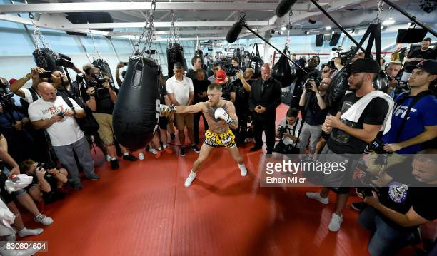 UFC lightweight champion Conor McGregor hits a heavy bag during a media workout at the UFC Performance Institute on August 11 2017 in Las Vegas...