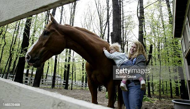 liisa Jackson and her daughter 18monthold Celia greet their horse Macho in the back yard paddock Some town residents want rural character and some...