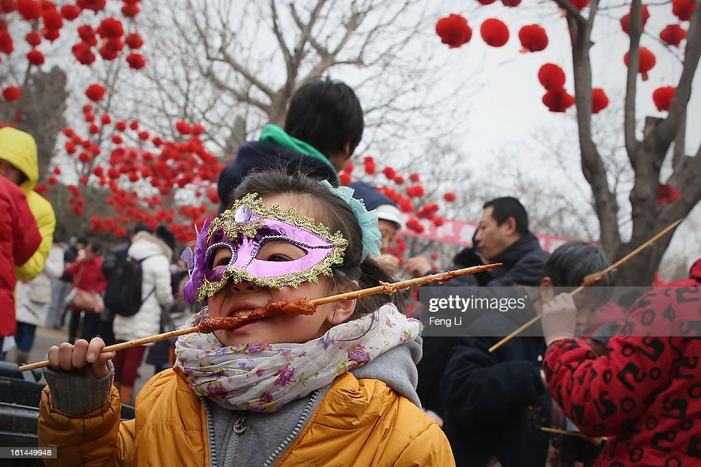 A liitle girl eats mutton skewer at a Spring Festival Temple Fair for celebrating Chinese Lunar New Year of Snake on February 11, 2013 in Beijing, China. The Chinese Lunar New Year of Snake also known as the Spring Festival, which is based on the Lunisolar Chinese calendar, is celebrated from the first day of the first month of the lunar year and ends with Lantern Festival on the Fifteenth day.