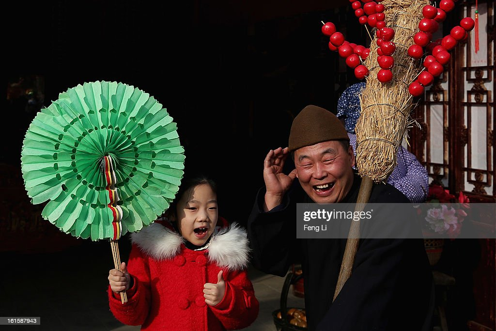 A liitle girl takes photo with a Chinese folk artist at a Spring Festival Temple Fair for celebrating Chinese Lunar New Year of Snake at the Temple of Earth park on February 12, 2013 in Beijing, China. The Chinese Lunar New Year of Snake also known as the Spring Festival, which is based on the Lunisolar Chinese calendar, is celebrated from the first day of the first month of the lunar year and ends with Lantern Festival on the Fifteenth day.