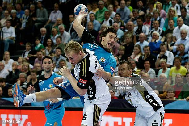 Lika Cindric of Metalurg challenges for the ball with Christian Zeitz of Kiel during the Velux EHF Champions League quarter final handball match...