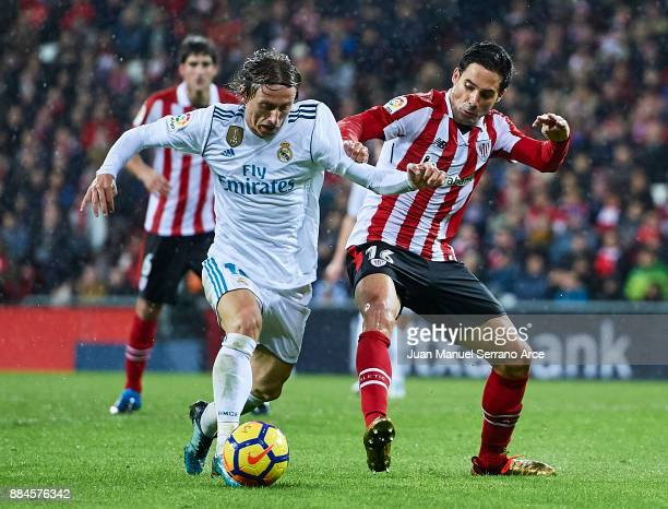 Lika Modric of Real Madrid CF is challenged by Xavier Etxeita of Athletic Club during the La Liga match between Athletic Club and Real Madrid at...