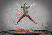Mid-air shot of beautiful young woman jumping on trampoline with confetti all around her