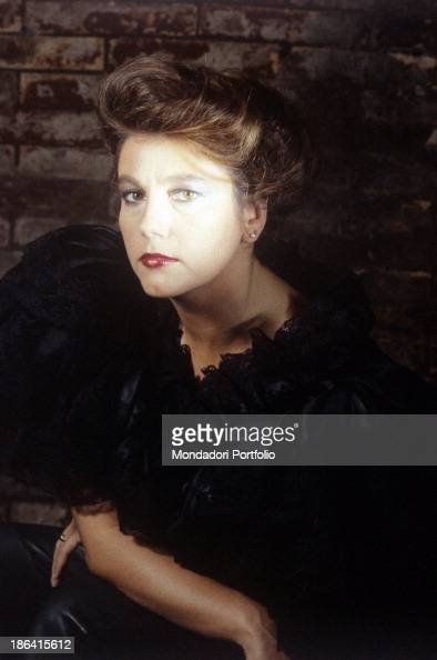 Like a timesgoneby diva the actress Stefania Sandrelli wears an elegant black blouse with wide sleeves and a lace collar and leather pants her hair...