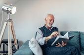 Elderly man reading a book